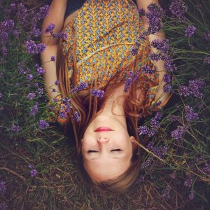 Young woman, smiling, lying in field of lavender.