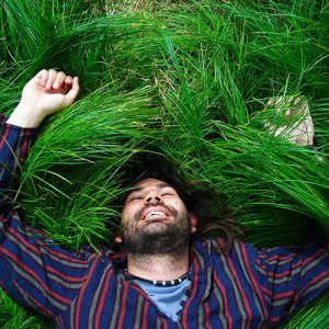 A man, smiling widely, is lying on the grass with his arms over his head.